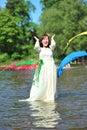 Das Mädchen in einem Hochzeitskleid goß durch einen Lack Lizenzfreies Stockfoto