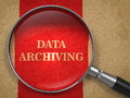 Data archiving magnifying glass concept on old paper with red vertical line background Stock Photo