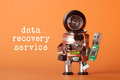 Data recovery service concept. Robotic character with usb flash stick. fun toy black helmet head green storage chip in Royalty Free Stock Photo