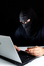 Data thief hooded stealing a laptop Royalty Free Stock Photography