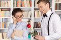 Date in library cheerful young nerd men giving a red rose to a beautiful young women glasses while standing at the Royalty Free Stock Images