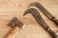 Dated and used cleaver and two billhooks on wooden background Royalty Free Stock Photography