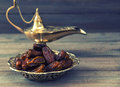 Dates and golden arabian lamp on wooden background. Oriental foo Royalty Free Stock Photo