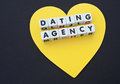 Dating agency text in uppercase black letters inscribed on small white cubes placed on a golden or yellow heart black background Stock Images
