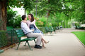 Dating couple hugging on a bench in a Parisian park Stock Images