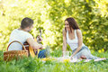 Dating picnic young men playing the guitar and flirting with a woman selective focus on woman Royalty Free Stock Photo