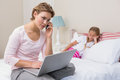 Daughter being ignored by busy mum at home in the bedroom Stock Images