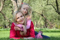 Daughter embraces mother lying on grass Stock Photos