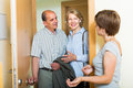 Daughter greeting parents at threshold positive adult smiling elderly Stock Image