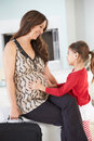 Daughter greeting pregnant mother home from work smiling and Royalty Free Stock Photo