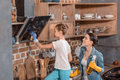 Daughter helping mother cleaning tv set at home