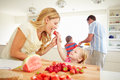 Daughter helping mother to prepare family breakfast eating strawberries Royalty Free Stock Images