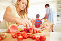 Daughter helping mother to prepare family breakfast in kitchen with strawberries on chopping board Royalty Free Stock Photos