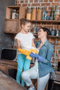 Daughter helping young mother with housework at home