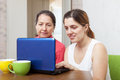 Daughter helps mature mother using laptop Stock Photo
