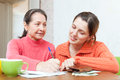 Daughter helps the mother to fills in utility payments adult bills Stock Images