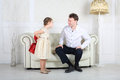 Daughter hides behind gift for father little and looks at his on sofa Stock Photo