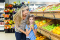 Daughter holding an apple at grocery shop Royalty Free Stock Photo