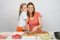 Daughter hugging her mother, which makes pizza Royalty Free Stock Photo