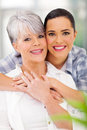 Daughter hugging mother loving middle aged at home Stock Photo