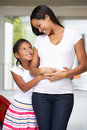 Daughter hugging pregnant mother and smiling Stock Image