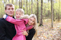 Daughter hugs father and mother peeks out from behind them happy in autumn forest focus on shallow depth of field Stock Image