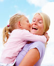 Daughter kissing her smiling mother Stock Images