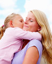 Daughter kissing her smiling mother Stock Photos