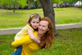 Daughter and mother piggyback smiling in park outdoor happy Royalty Free Stock Photo