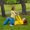 Daughter and mother playing lying on park lawn outdoor dressed in yellow Royalty Free Stock Photography