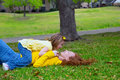 Daughter and mother playing lying on park lawn outdoor dressed in yellow Stock Photos