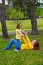 Daughter and mother playing lying on park lawn outdoor dressed in yellow Stock Images