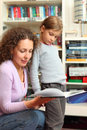 Daughter with mother read book in room Royalty Free Stock Photo