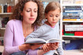 Daughter with mother read book in room Royalty Free Stock Photography
