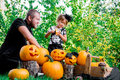Daughter near father who pulls seeds and fibrous material from a pumpkin before carving for Halloween. Prepares jack-o-lantern. D Royalty Free Stock Photo