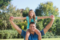 Daughter sitting on dads shoulder and stretching her arms in the park Royalty Free Stock Photos