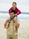 A daughter sitting on her father s shoulders and pulling his ears at the beach Stock Photo