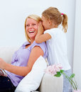 Daughter whispering to her smiling young mother Stock Photo
