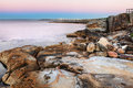 Dawn at botany bay australia first light before sunrise with beautiful multi coloured sandstone rocks and boulders in the Stock Photos