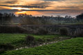 Dawn over railway tracks through countryside landscape