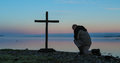 Dawn praying man kneeling in pray before a cross with a morning mist over a lake in the background Stock Photo