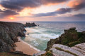 Dawn on treen cliffs cornwall dramtic sunrise over pednvounder beach and logans rock from near porthcurno england uk Stock Image