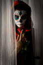 Day of the dead girl with sugar skull makeup holding red rose Royalty Free Stock Images