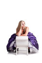 Day dreaming princess a pretty caucasian girl wearing a purple ball gown sitting on a white chair with her hand in her hair Stock Image