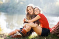 Day off with friend two young women sitting on grass having good time Stock Photography