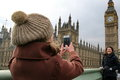 Day out in london a daughter takes a picture of her mother on a smart phone on a with a backdrop of big ben the houses of Stock Image