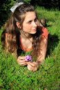 Daydreamer teen lounging a pretty teenaged girl with a bow in her long brown hair in the grass with thoughts in her head shallow Stock Image