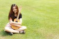 Daydreaming girl a beautiful asian thai is sitting in a park holding a guitar on green grass background Royalty Free Stock Image