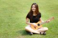 Daydreaming girl a beautiful asian thai is sitting in a park playing guitar on green grass background Stock Images