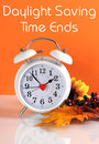 Daylight savings time ends in autumn fall with clock concept and text message